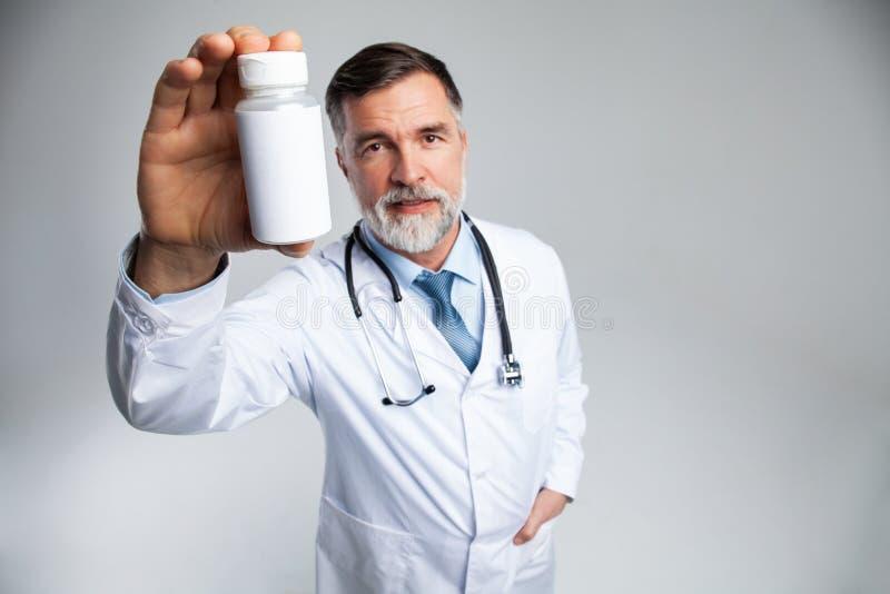 Le doktorn som upp rymmer en flaska av minnestavlor eller piller med en tom vit etikett f?r behandling av en sjukdom eller en ska fotografering för bildbyråer