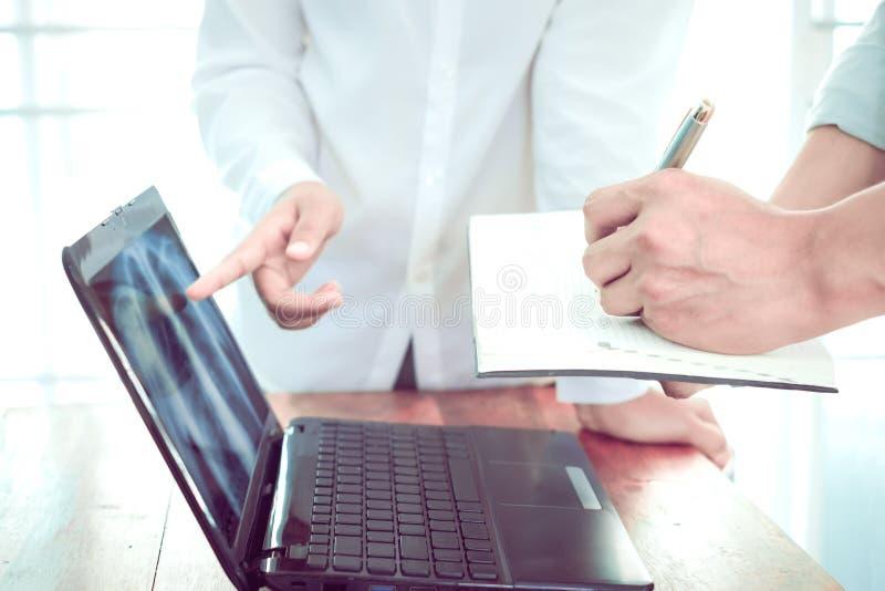 Le donne aggiustano e gli uomini aggiustano la discussione circa i raggi x pazienti del ` s sul computer portatile fotografia stock libera da diritti
