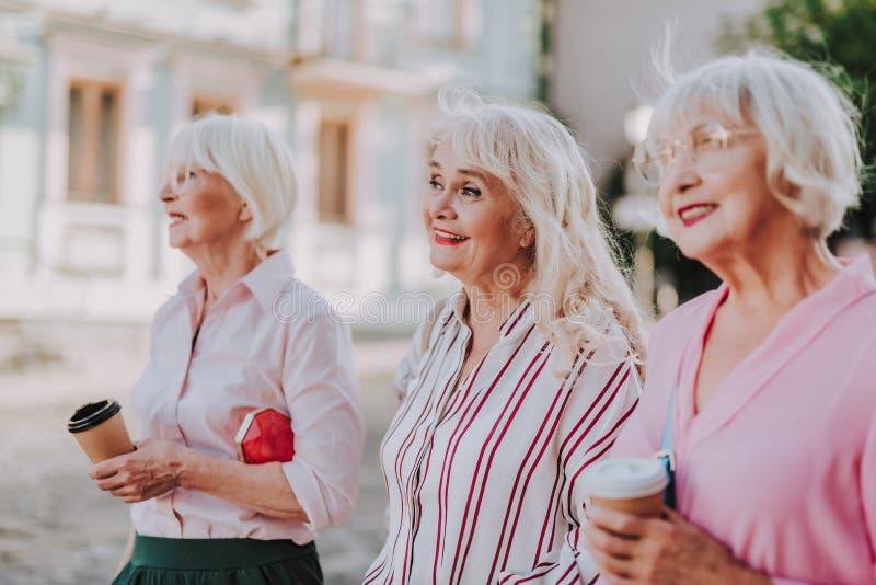 Le donne anziane sorridenti stanno bevendo un caffè immagini stock