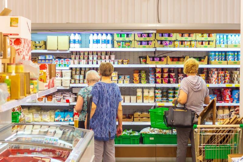 Le donne anziane stanno davanti agli scaffali della drogheria in un deposito e pensano che cosa comprare fotografia stock libera da diritti