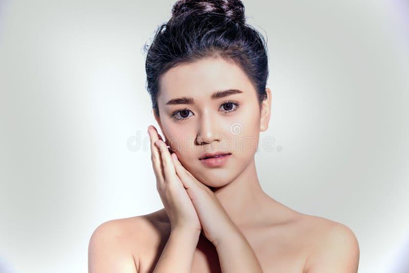 Le donne asiatiche belle con pelle fresca pulita toccano per possedere il fronte Trattamento facciale Cosmetologia, bellezza e st fotografia stock libera da diritti