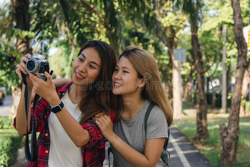 Le donne asiatiche dell'amico del bello viaggiatore felice portano lo zaino Donne asiatiche del giovane amico allegro che usando  fotografia stock