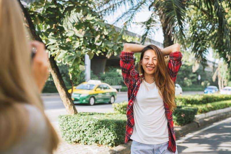 Le donne asiatiche dell'amico del bello viaggiatore felice portano lo zaino Donne asiatiche del giovane amico che usando macchina immagini stock