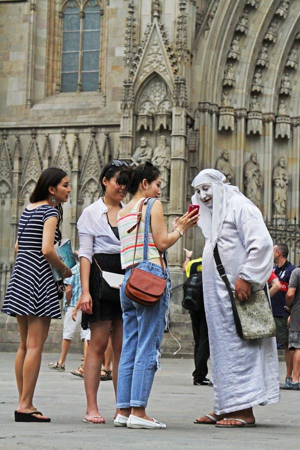 Le donne asiatiche mostrano le foto ad un artista della via su uno smartphone sulle vie di Barcellona fotografie stock