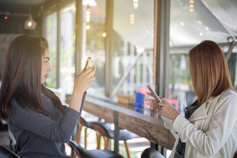 Le donne asiatiche prendono le foto ad un amico immagini stock libere da diritti