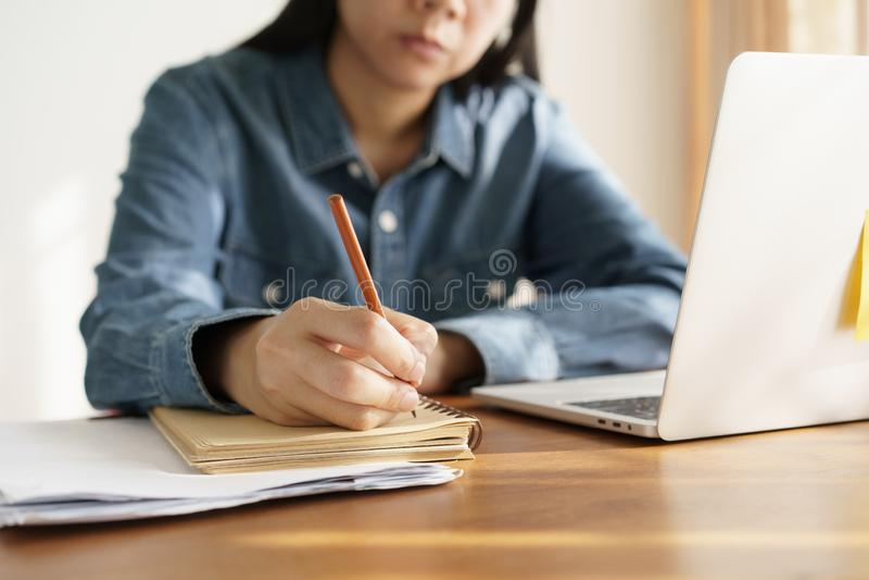 Le donne asiatiche prendono le note con una matita nell'ufficio, funzionamento della donna di affari fotografia stock