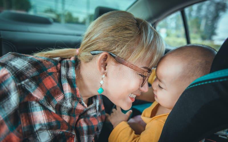 Le donne asiatiche stanno prendendo la cura del loro figlio in sua automobile immagine stock