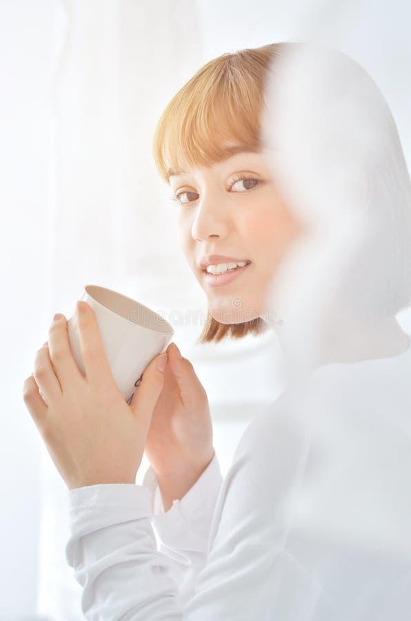 Le donne bevono il giardino del caff? di mattina fotografie stock