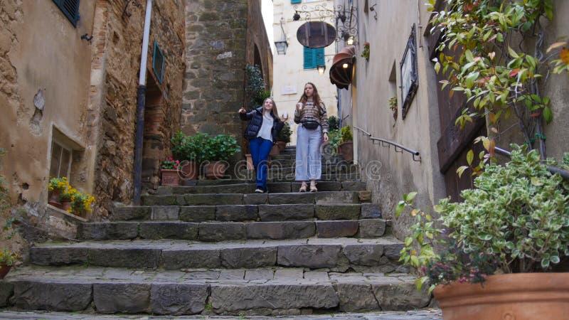Le donne camminano giù le scale - beva il caffè e guardi intorno fotografie stock libere da diritti