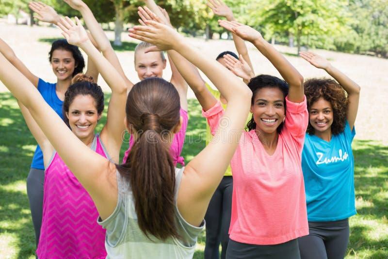 Le donne che eseguono la forma fisica ballano con l'istruttore al parco immagini stock libere da diritti