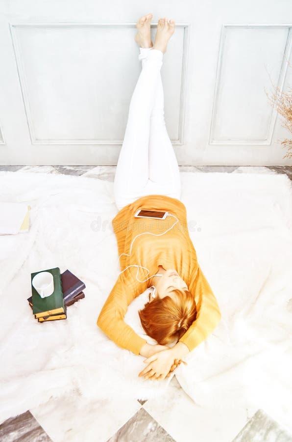 Le donne che portano le camice arancio stanno ascoltando musica e sono felici immagini stock