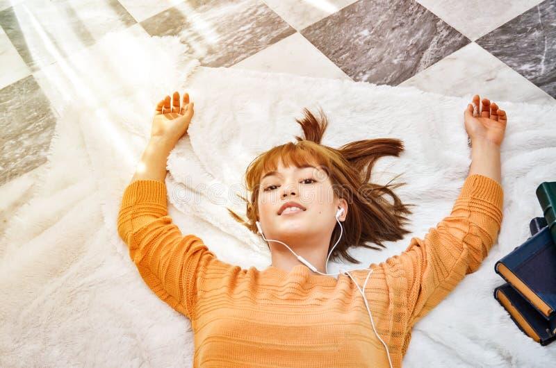 Le donne che portano le camice arancio stanno ascoltando musica e sono felici fotografie stock libere da diritti