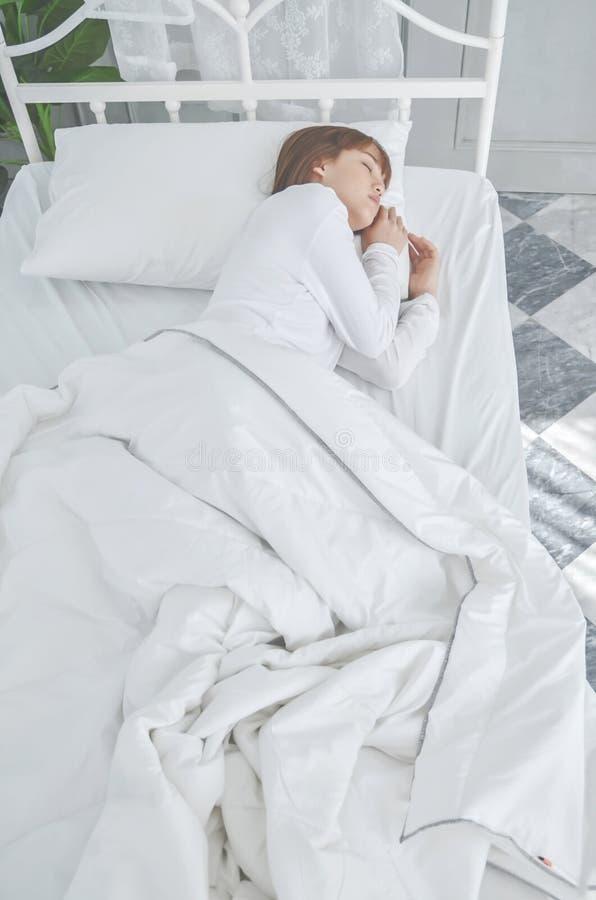 Le donne che portano i pigiami bianchi riposano sul materasso immagini stock