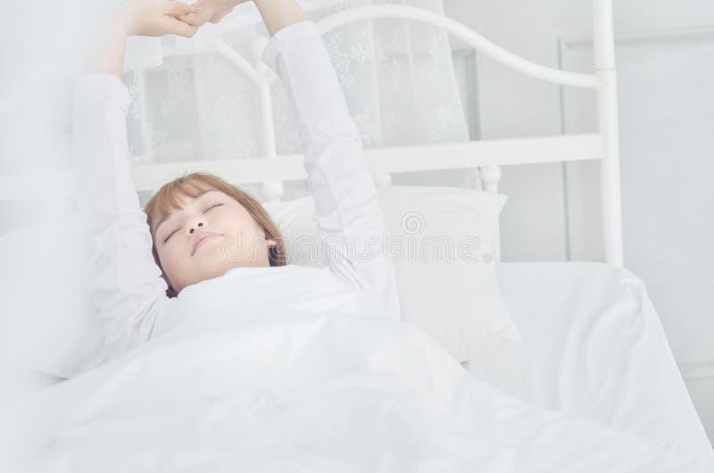 Le donne che portano i pigiami bianchi riposano sul materasso fotografia stock