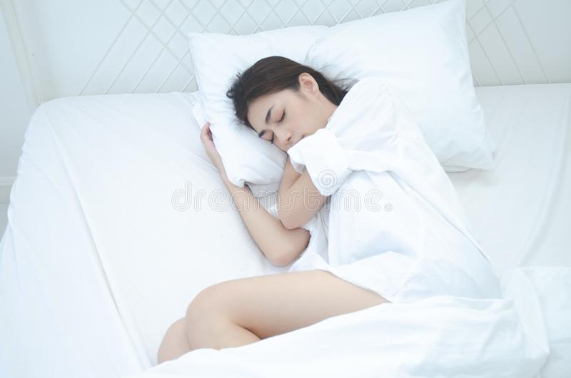 Le donne che portano i pigiami bianchi stanno riposando fotografie stock libere da diritti