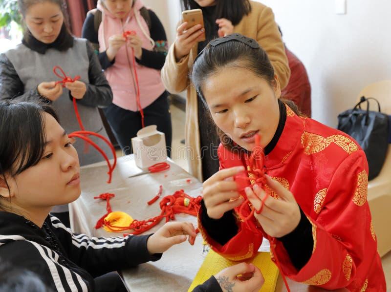 Le donne cinesi imparano fare l'annodamento fortunato cinese immagini stock