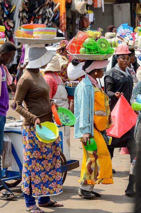 Le donne del Ghana non identificate portano i bacini con le merci sul thei fotografie stock libere da diritti
