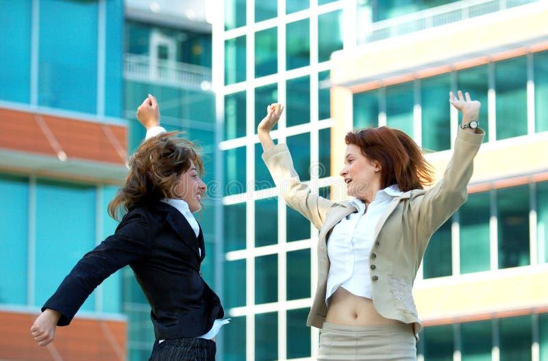 Le donne di affari saltano per la gioia immagine stock