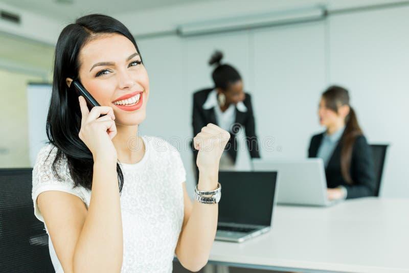 Le donne di affari in un ufficio che lavora ad un computer portatile e che chiama poten fotografie stock libere da diritti