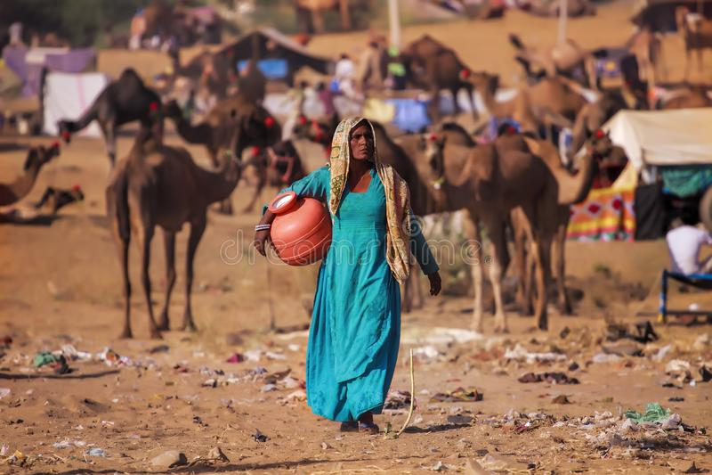 Le donne di Pushkar prende l'acqua da un bacino dell'acqua immagini stock