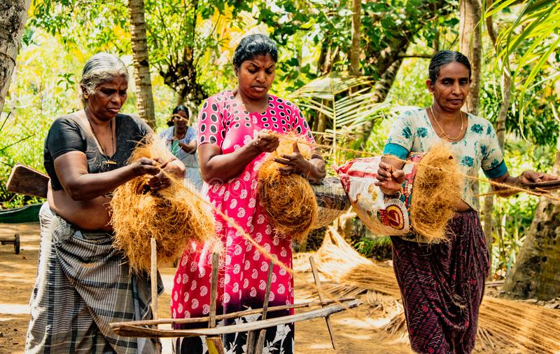 Le donne filano a mano i capelli della noce di cocco, trasformandolo in una forte corda immagine stock