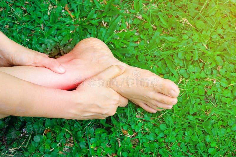 Le donne giudicano la sua caviglia storta causata da un incidente Dolore ritenente danneggiato della persona ed usando la tenuta  fotografia stock libera da diritti