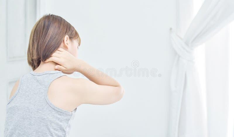 Le donne hanno preso le loro mani al collo Ha dolore nel suo collo immagini stock