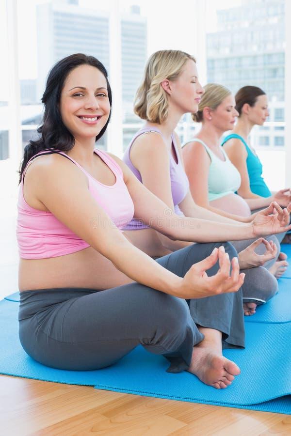 Le donne incinte contente che meditano nell'yoga classificano con una che sorride alla macchina fotografica fotografia stock libera da diritti