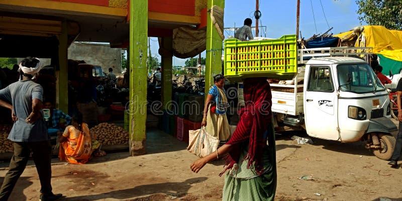 Le donne indiane hanno rinviato il canestro di verdure del contenitore sopra la testa fotografie stock
