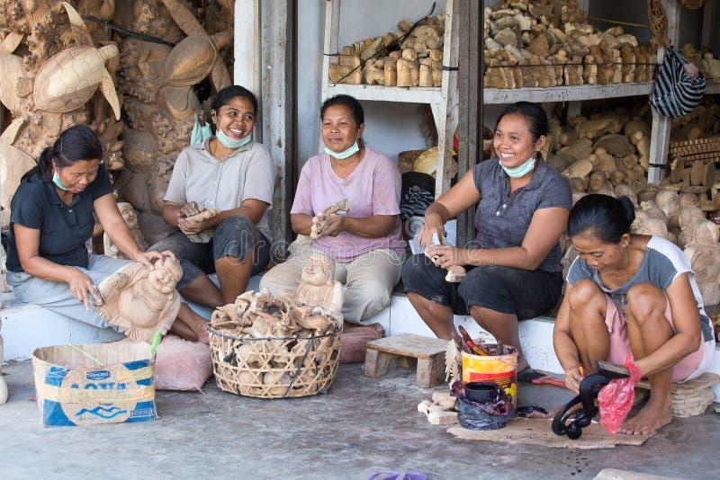 Le donne indonesiane stanno facendo i ricordi di legno per il turista Ubud, Bali l'indonesia fotografie stock libere da diritti