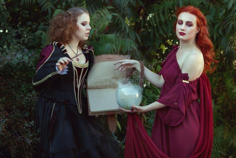 Le donne leggono un libro magico ed emettono i periodi fotografia stock