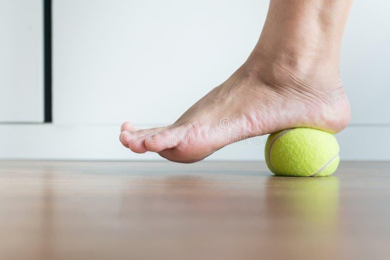 Le donne massaggiano con pallina da tennis al suo piede in camera da letto, piedi di massaggio delle sogliole per le fascite plan fotografia stock