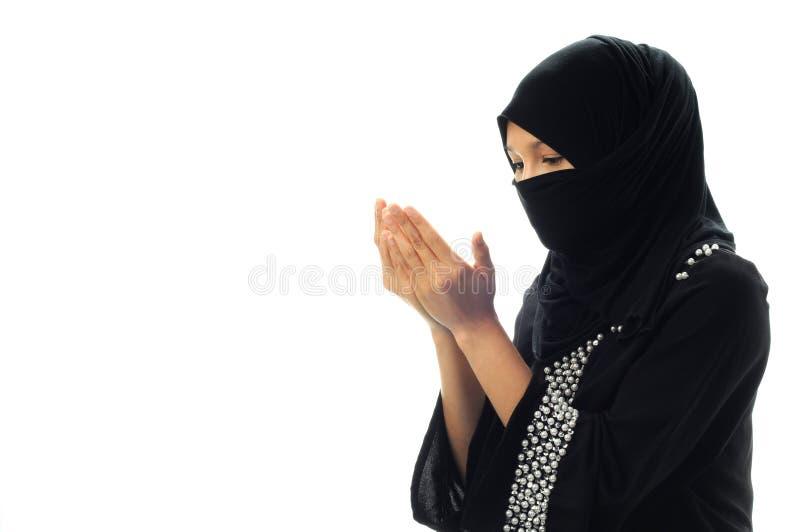 Le donne musulmane pregano lo sguardo giù da largo laterale immagini stock