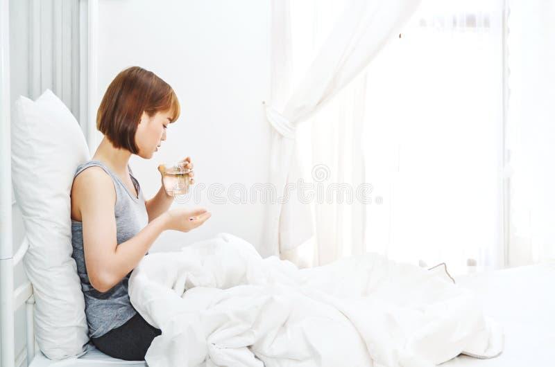 Le donne non sono pillole comode del cibo sul materasso immagini stock libere da diritti