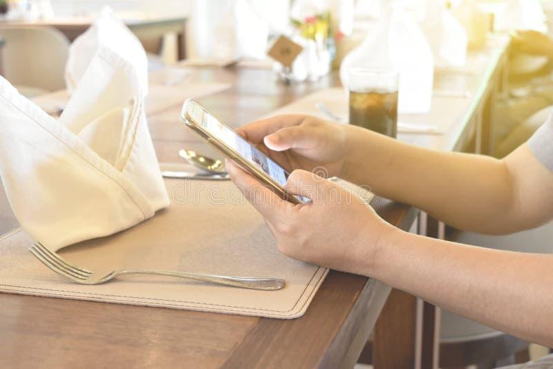 Le donne passano facendo uso del telefono su stoviglie in ristorante fotografia stock libera da diritti
