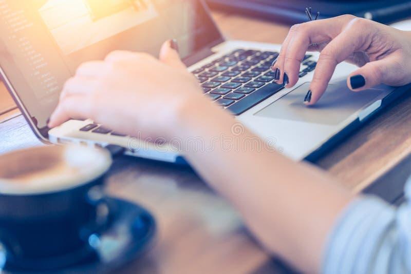Le donne passano il lavoro con il caffè della bevanda del computer portatile fotografia stock
