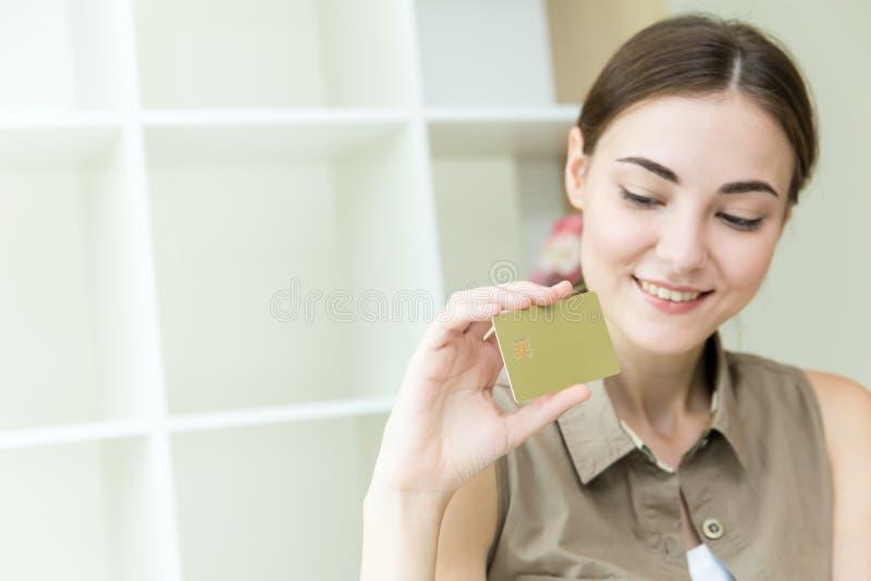 Le donne passano la carta di credito della tenuta per acquisto online immagine stock