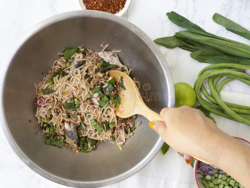 Le donne passano la tagliatella di riso piccante mescolantesi con l'insalata del pesce dello sgombro fotografia stock libera da diritti