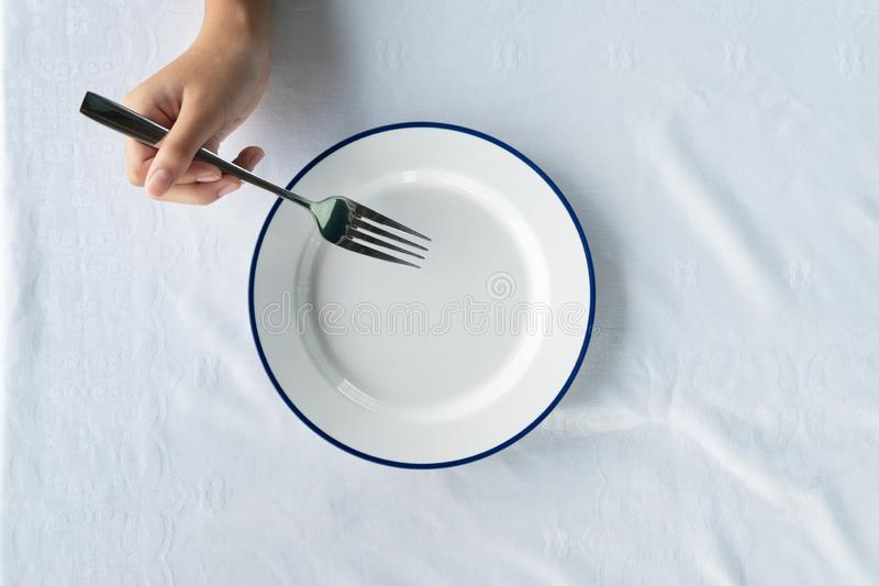 Le donne passano la tenuta della forcella del metallo per alimento che mangiano con il piatto blu bianco vuoto dello smalto sul f fotografie stock