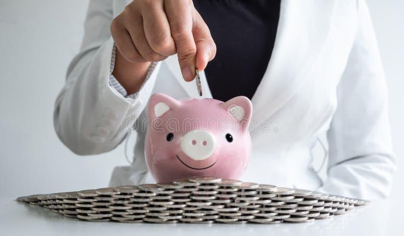 Le donne passano mettere la moneta nei soldi di risparmio del porcellino salvadanaio rosa con il bunker delle monete fotografie stock