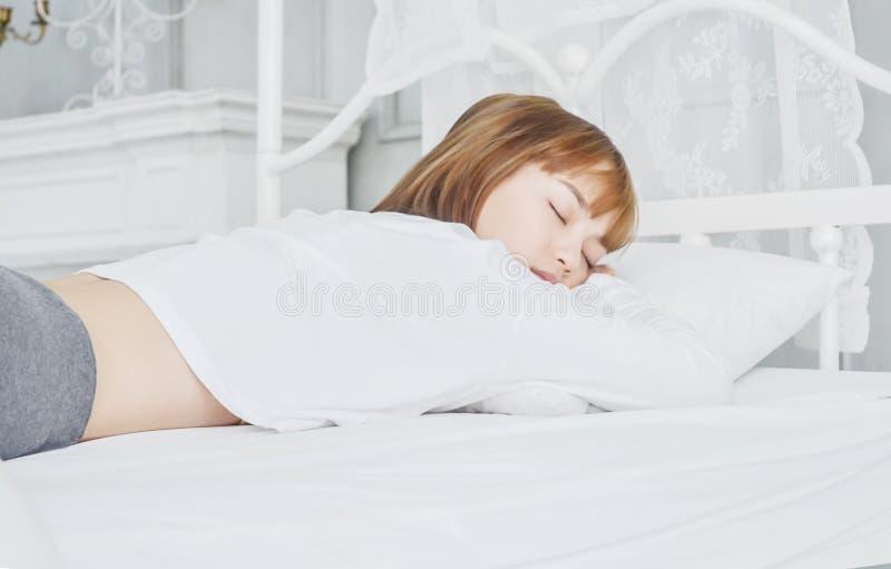 Le donne portano i pigiami bianchi sul materasso fotografia stock libera da diritti
