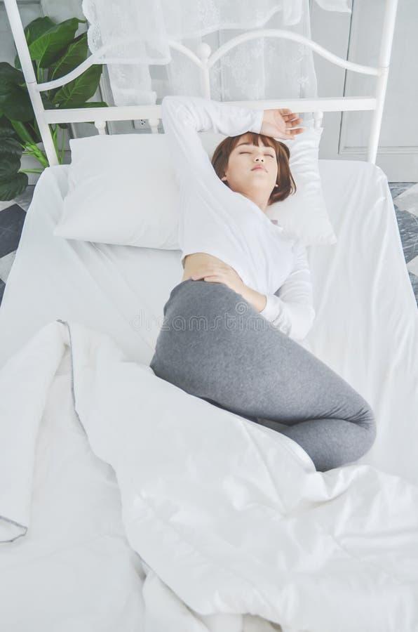 Le donne portano i pigiami bianchi sul materasso immagine stock libera da diritti
