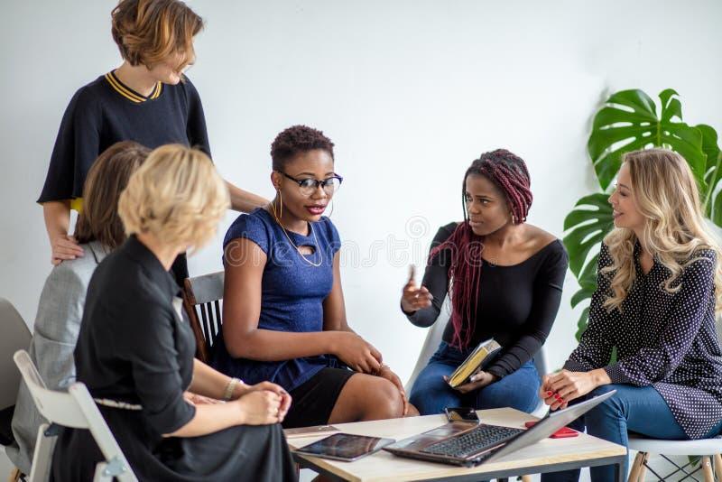 Le donne positive discutono il piano dell'organizzazione mentre si siedono alla tavola con il computer portatile fotografie stock libere da diritti