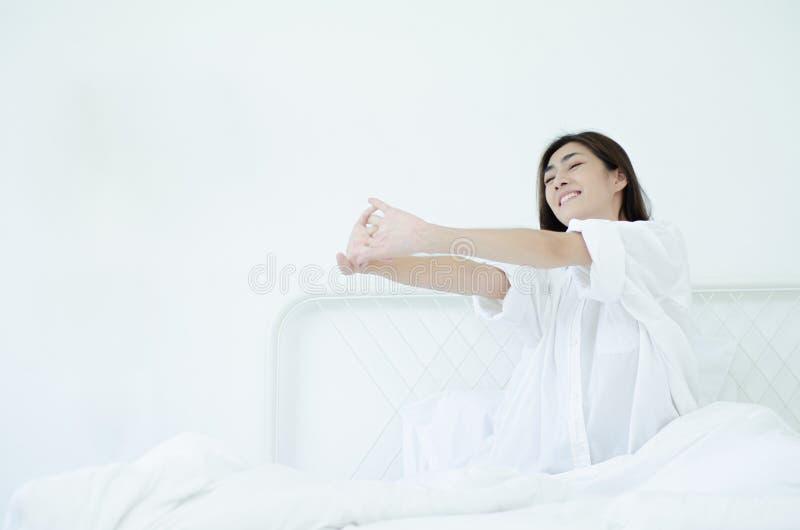 Le donne si siedono al bordo del letto fotografie stock