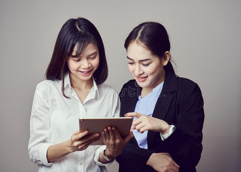 Le donne sorridenti di affari stanno tenendo la compressa ed usando i moduli di iscrizione online fotografia stock libera da diritti
