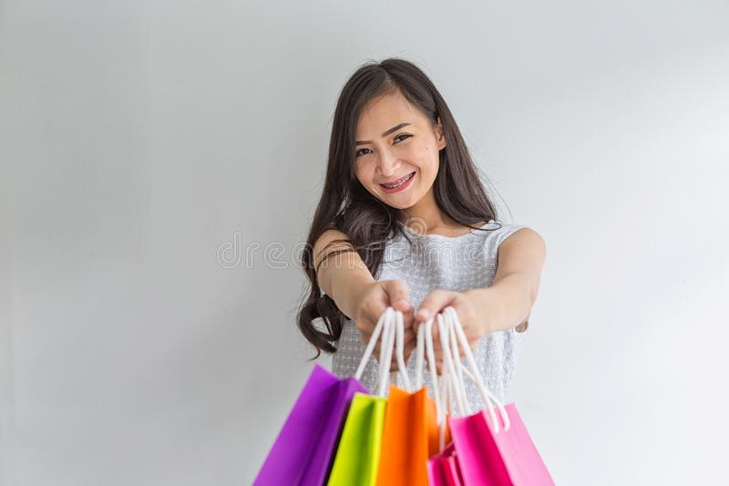 Le donne sottopongono i sacchetti della spesa a voi Giovane cliente Sorridere della donna di acquisto Bella ragazza asiatica immagini stock libere da diritti