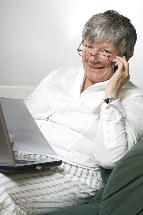 Le donne sta lavorando al computer portatile ed a chiamare fotografia stock libera da diritti