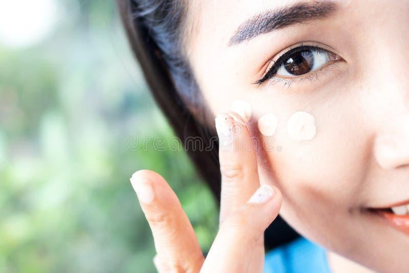 Le donne stanno applicando il correttore sotto gli occhi fotografie stock