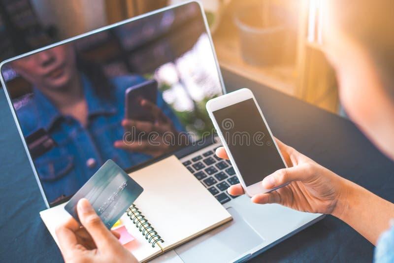 Le donne tengono le carte di credito ed utilizzano i telefoni cellulari alla compera online immagine stock