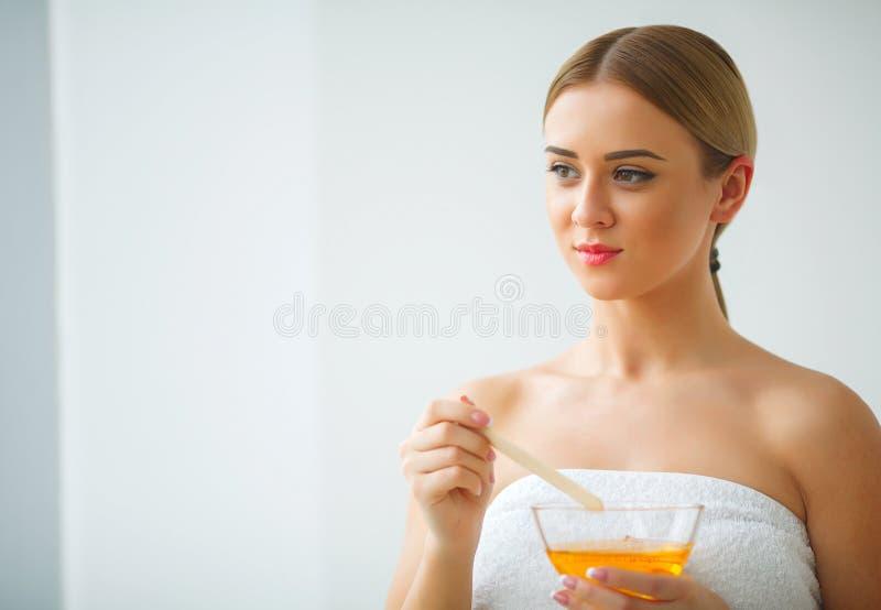 Le donne tengono la ciotola arancio della cera paraffinica Donna nel salone di bellezza immagini stock